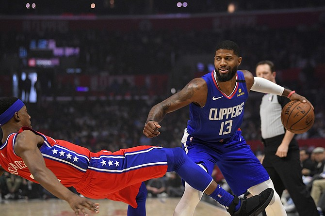 Philadelphia 76ers guard Josh Richardson, left, goes down as Los Angeles Clippers guard Paul George tries to drive past him during the first half of an NBA basketball game Sunday, Mar. 1, 2020, in Los Angeles.