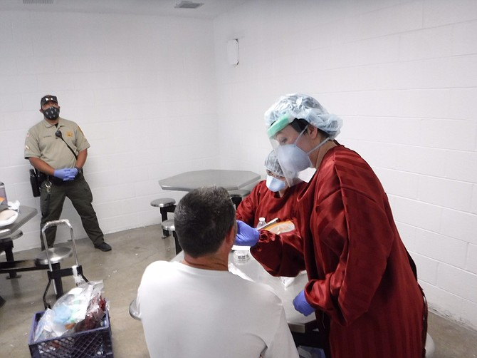 A NDOC nurse tests an offender for COVID-19 under the watchful eye of a correctional officer.