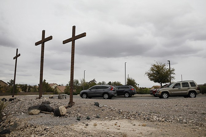 Cars stop at a station at a drive-thru Stations of the Cross for social distancing due to the coronavirus on Good Friday at the New Song church, Friday, April 10, 2020, in Henderson, Nev. (AP Photo/John Locher)