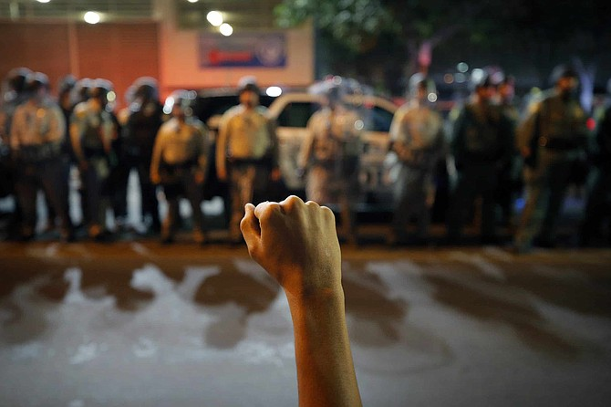A protester raises his fist during a rally Monday, June 1, 2020, in Las Vegas, against police brutality sparked by the death of George Floyd, a black man who died after being restrained by Minneapolis police officers on May 25.