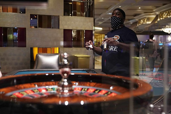 Dred Phillips plays roulette at the reopening of the Bellagio hotel and casino Thursday, June 4, 2020, in Las Vegas. Casinos in Nevada were allowed to reopen on Thursday for the first time after temporary closures as a precaution against the coronavirus.