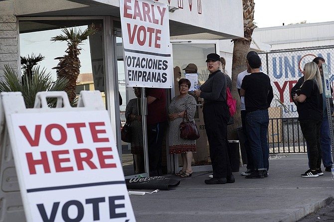 FILE - In this Feb. 15, 2020 file photo, people wait in line at an early voting location at the culinary workers union hall in Las Vegas. Nevada is attempting a high-wire act of holding its first-ever election almost entirely by mail, reflecting a new law allowing voters to register at the polls while keeping people safe amid the pandemic. Secretary of State Barbara Cegavske limited the number of polling places for the Tuesday, June 9, 2020, primary and instead sent absentee ballots to voters. (AP Photo/John Locher, File)