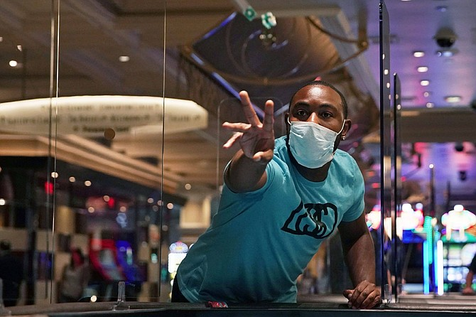 FILE - In this June 4, 2020 file photo, a man plays craps at the reopening of the Bellagio hotel and casino.