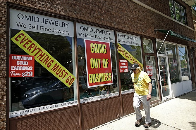 A man walks past a retail store that is going out of business due to the coronavirus pandemic in Winnetka, Ill., Tuesday, June 23, 2020. Illinois Gov. J.B Pritzker announced a package of state grant programs that will help support communities and businesses impacted by the COVID-19 pandemic and unrest in the area.