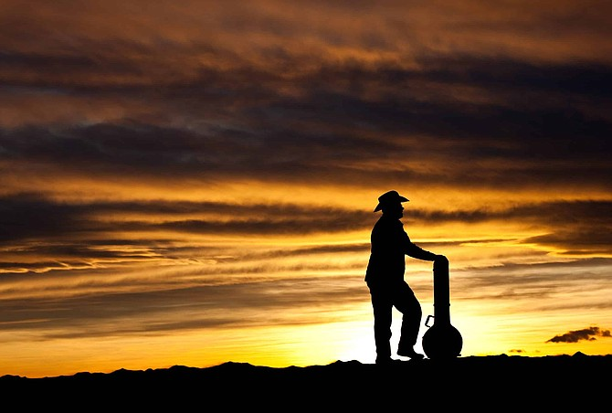 A silhouette of a country musician standing with a banjo. Cowboy. Dramatic sunset. Relaxed. Poet.