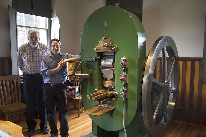 Bob Nylen, former curator of history at the Nevada State Museum, Carson City, and Myron Freedman, acting administrator for the Nevada Division of Museums and History, stand by Coin Press No. 1, at the Nevada State Museum in Carson City.