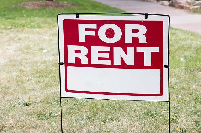 "Image of a blank red and white ""For Rent"" sign posted on the short grass of a front yard.  The For Rent sign is advertising to rent a home.  There is a sidewalk behind the blank sign."