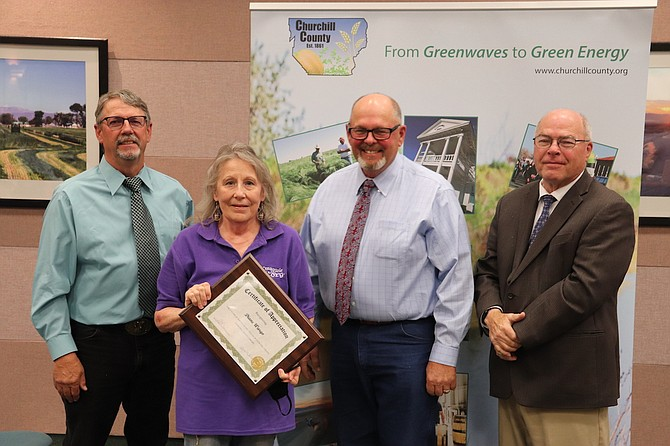 Commissioners Carl Erquiaga, left, Pete Olsen and Bus Scharmann present an Employee Service Award to Diane Wargo, second from left, Churchill County Library, for 25 years.