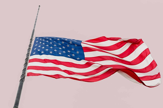 United States Flag Flying at a Half-staff Waving Against Gray Sky