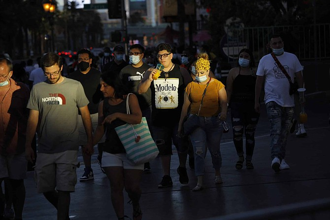 FILE - In this Saturday, July 4, 2020 file photo people, some clad in masks as a precaution against coronavirus, walk along the Las Vegas Strip on the Fourth of July in Las Vegas. Nevada officials say a record high in the daily number of positive COVID-19 tests in the state may be the result of people failing to wear masks and keep distances apart during the Independence Day holiday.