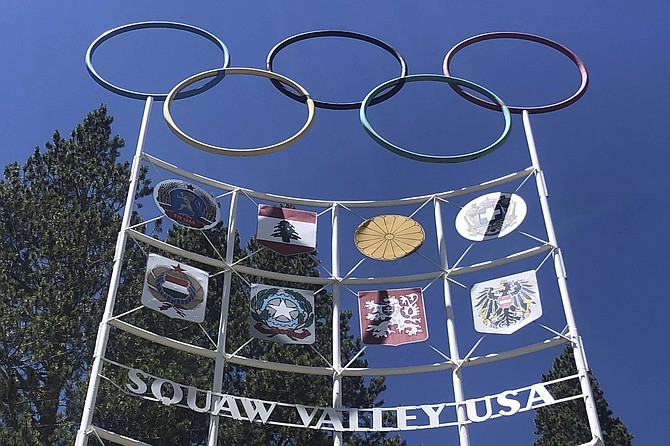 """The Olympic rings stand atop a sign at the entrance to the Squaw Valley Ski Resort in Olympic Valley, Calif., July 8, 2020. California's Squaw Valley Ski Resort is considering changing its name to remove """"squaw,"""" a derogatory term for Native American women. Squaw Valley President & CEO Ron Cohen says resort officials are meeting with shareholders and the local Washoe tribal leadership to get their input. He says he can't give a timeline on when the decision will be made. The renaming of Squaw Valley Ski Resort is one of many efforts across the nation to address colonialism and indigenous oppression."""