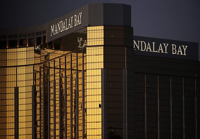 FILE - In this Oct. 3, 2017, file photo, windows are broken at the Mandalay Bay resort and casino in Las Vegas, the room from where Stephen Craig Paddock fired on a nearby music festival, killing 58 and injuring hundreds on Oct. 1, 2017. A coroner in Southern California has attributed the death of a woman to wounds she received in the Las Vegas mass shooting in October 2017. The decision by authorities in San Bernardino County would add Kimberly May Gervais to the list of 58 people killed in the deadliest mass shooting in modern American history.