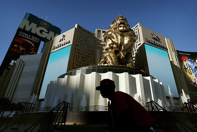 FILE - In this Aug. 3, 2015, file photo, a man rides his bike past the MGM Grand hotel and casino in Las Vegas.   MGM Resorts plans to lay off 18,000 workers as the casino company struggles with the fallout from the pandemic. The Las Vegas-based parent of the Bellagio said in a letter to employees that furloughed employees will keep health benefits until Sept. 30, 2020 according to a report in The Wall Street Journal.