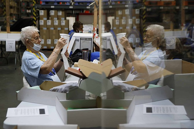 FILE - In this June 9, 2020, file photo election workers process mail-in ballots during a nearly all-mail primary election in Las Vegas.