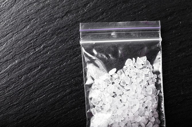 drugs in the form of crystals on a black background, methamphetamine in a plastic bag