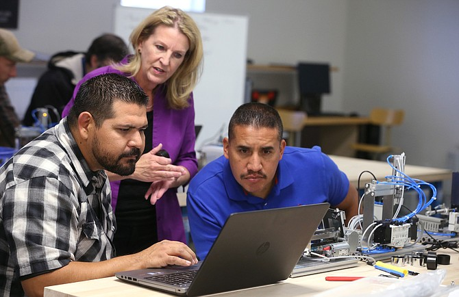 AIT Professor Emily Howarth talks with Ricardo Fregoso and Ezequiel Varela during a lab at Western Nevada College in Carson City, Nev., on Thursday, Oct. 5, 2017.