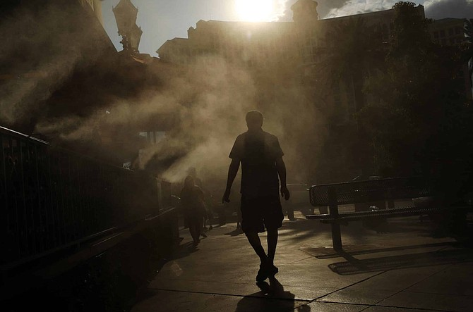 File - In this July 26, 2018, file photo, a man cools off in a water mist along the Las Vegas Strip in Las Vegas.