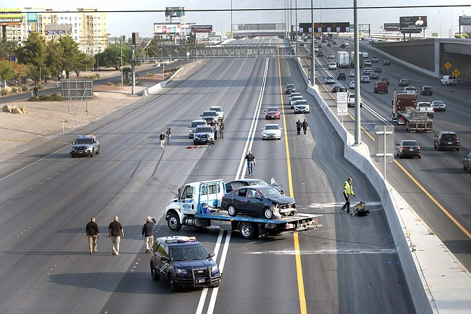 Las Vegas Metro Police investigators and crime scene analysts work the scene of a crash on I-15 southbound in Las Vegas Wednesday, Sept. 16, 2020.  A driver found dead after the crash on the busy freeway overnight had been shot in the head, and investigators are trying to unravel what might have been a road rage killing, a police official said Wednesday.