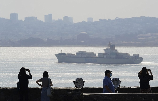 People stand at a vista point and look out toward the the San Francisco skyline obscured by smoke from wildfires as a container ship passes Monday, Sept. 28, 2020, near Sausalito, Calif. (AP Photo/Eric Risberg)