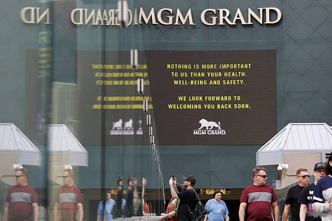 "FILE - The MGM Grand hotel-casino, flashes messages on their marquees that reads ""Nothing is more important to us than your health, well-being and safety. We look forward to welcoming you back soon."", in Las Vegas In this March 16, 2020 file photo. Casino giant MGM Resorts International said Tuesday, Sept. 29, 2020, it's teaming with a firm that provided COVID-19 screenings to the National Hockey League playoffs and a health care provider to high-volume events in an optional conference attendee safety plan at its U.S. hotels and casinos."