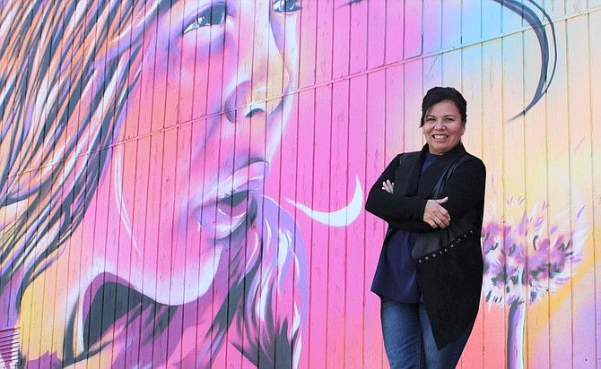 Brewery Arts Center Executive Director Gina Lopez stands in front of the Bryce Chisholm mural commissioned by the Downtown Business Association.