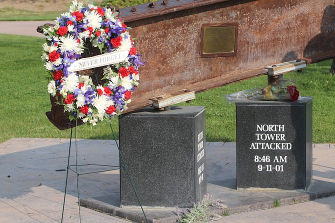 A wreath with a ribbon of Never Forget keeps watch on blocks noting the attacks on the north and south towers of the World Trade Center.