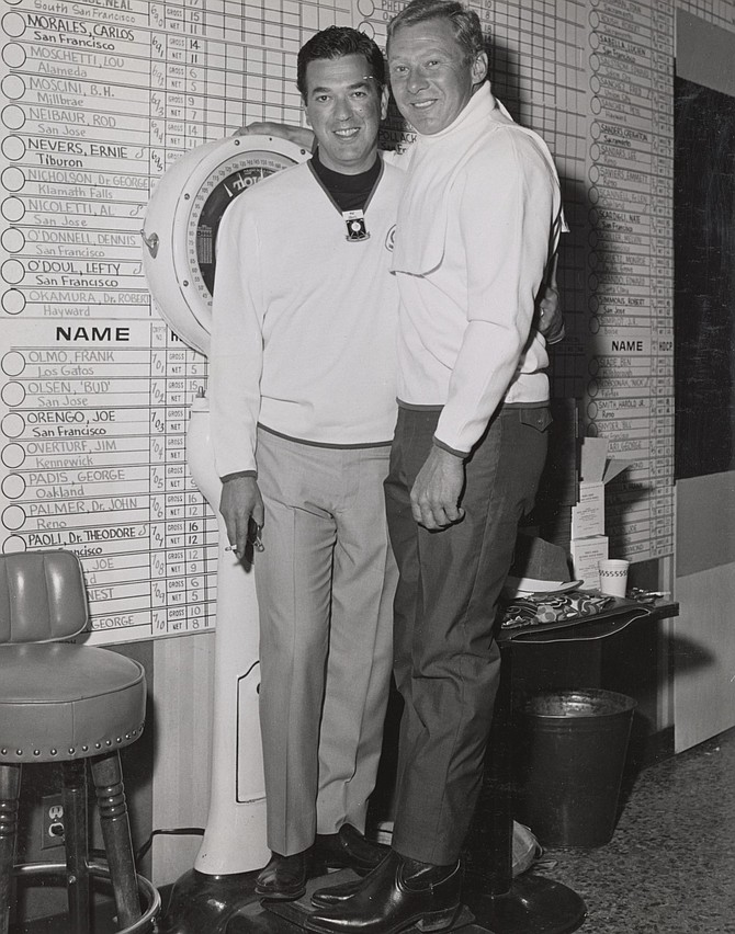 Mal Alberts and Jackie Jensen wearing white sweaters and standing in front of the wall with the list of players participating in the Nugget Golf Classic in 1967.