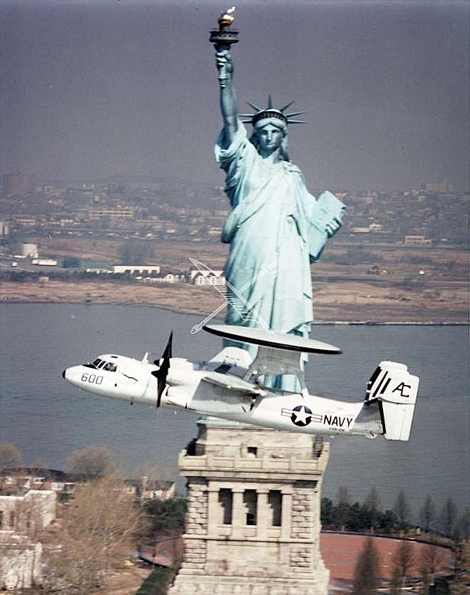 An E-2C, an all-weather airborne early warning aircraft, flies past the Statue of Liberty.