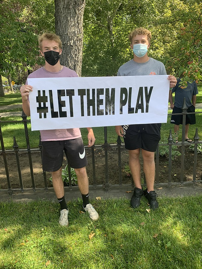 Douglas High School athletes Christopher Smalley, left, and Cameron Swain stand with a #LetUsPlay sign outside of the Nevada State Capitol Saturday afternoon as about 125 people protested to resume athletic events in the state of Nevada.