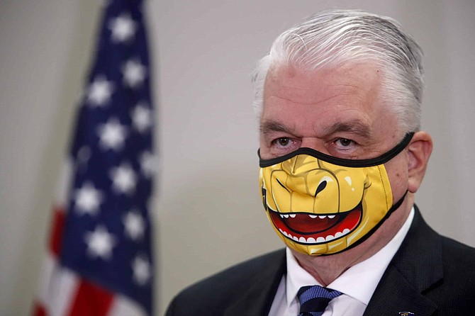 Nevada Governor Steve Sisolak speaks during a news conference at the Grant Sawyer State Building in Las Vegas, Tuesday, Sept. 29, 2020. The governor provided updates on Nevada's COVID-19 response efforts and adjustments to current capacity limits on gatherings. The face mask is themed after the Vegas Golden Knights' mascot Chance the Golden Gila Monster. (Steve Marcus/Las Vegas Sun via AP, Pool)