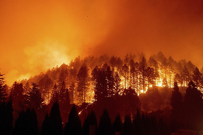 FILE - In this Sept. 27, 2020 file photo the Glass Fire burns a hillside above Silverado Trail in St. Helena, Calif.