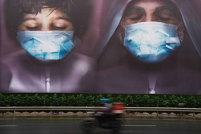 FILE - In this Wednesday, April 15, 2020 file photo, a motorcycle delivery man rides past a billboard urging people to stay home over the coronavirus pandemic in Dubai, United Arab Emirates. U.S. diplomats and security officials privately warned the state of Nevada not to use Chinese-made coronavirus test kits donated by the United Arab Emirates over concerns about patient privacy, test accuracy and Chinese government involvement, documents obtained by The Associated Press show.
