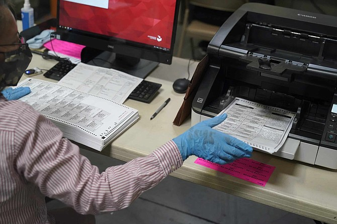 A county worker loads mail-in ballots into a scanner that records the votes at a tabulating area at the Clark County Election Department, Thursday, Oct. 29, 2020, in Las Vegas.