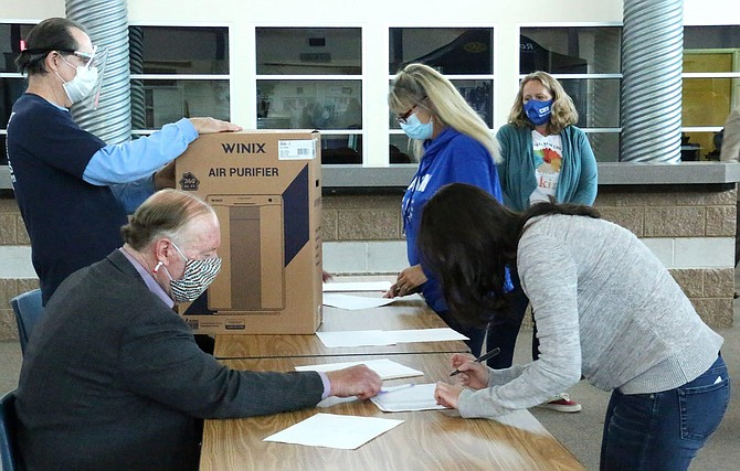 Rotary Club members Joe Walls, far left, and Ernie Adler assist in the distribution of the purifiers Monday at Carson High School by asking for staff members to sign for their boxes. In the right forefront, CHS math teacher Shanell Cavener signs for her purifier.