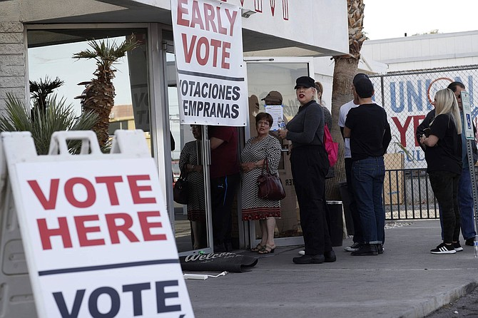"FILE - In this Feb. 15, 2020 file photo, people wait in line at an early voting location at the culinary workers union hall in Las Vegas. Nevada Attorney General Aaron Ford said Thursday, Oct. 1, 2020, he is worried about the possibility of voter intimidation after President Donald Trump implored supporters to ""watch very carefully"" at the polls. State prosecutors plan strict enforcement, Ford said in an interview."
