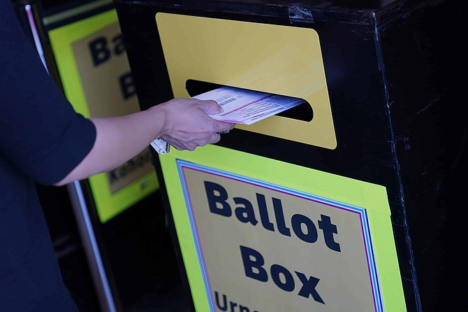 A person places mail-in ballots at a mail-in ballot drop box at the Clark County Election Department, Thursday, Oct. 29, 2020, in Las Vegas. (AP Photo/John Locher)