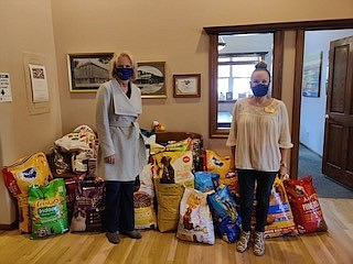 Victoria Williams, right, Coldwell Banker Select managing broker, presents more than 435 pounds of pet food to Genevieve Frederick, left, founder and president of Feeding Pets of the Homeless.