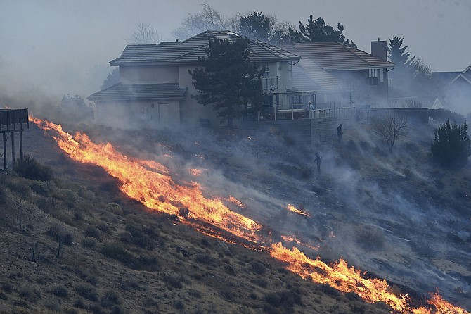 FILE - In this Nov. 17, 2020, file photo, people try to protect their homes during the Pinehaven Fire in the Caughlin Ranch area of Reno, Nev. Fire investigators say arcing power lines in gale force winds started a brush fire that destroyed five homes and damaged two dozen others in a south Reno neighborhood in the foothills along the Sierra in November. Reno Fire Marshal Tray Palmer said Tuesday, Jan. 19, 2021, they investigated but ruled out the possibility the Pinehaven Fire in Caughlin Ranch was caused by a campfire, target shooters or off-road enthusiasts on motorcycles or ATVs. (Jason Bean/The Reno Gazette-Journal via AP, File)