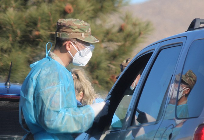 A tester from the Nevada Air Guard talks to a participant in coronavirus testing in December 2020.