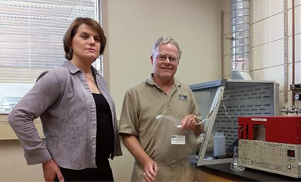 Lauren Scott, left, CEO and founder of Alkcon Corporation, with Kent Hoekman of Desert Research Institute with a gas analizer at DRI used to test gas samples from Alkcon. Hoekman, who has a Ph.D. in organic chemistry, is a technical advisor to Alkcon regarding the company's patent pending process to convert methane to biopropane.