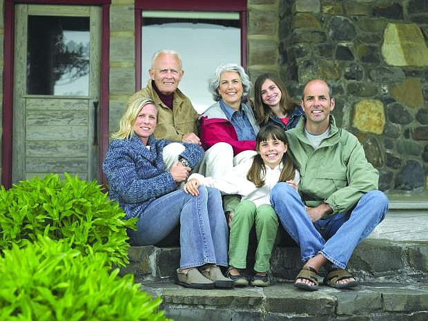 Three generation family sitting on steps in front of house, smiling portrait