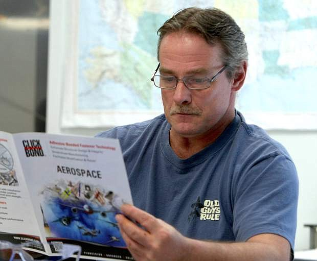 Machine tool technology student Thomas McDonough peruses a brochure during a presentation from Click Bond Inc.representative Larry Harvey on the first day of class Monday.