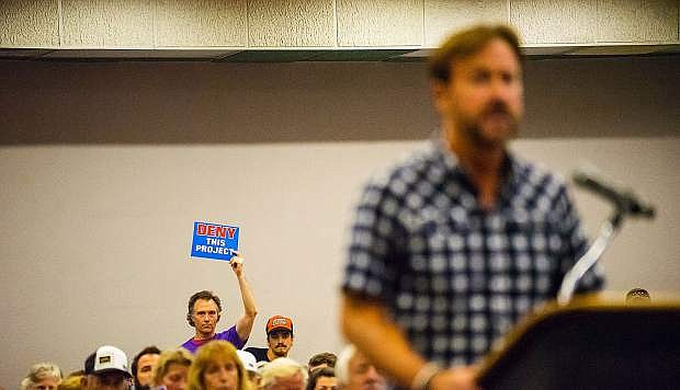 A person donning a Keep Squaw True T-shirt holds up an anti-project sign during the Aug. 11 meeting, while Squaw Valley Ski Holdings CEO Andy Wirth addresses the commission.