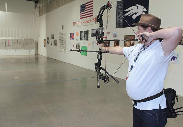 Lystra Pitts, owner of Wasting Arrows archery range in South Meadows, takes aim at a target 60 feet away.