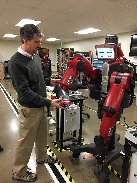Kyle Dalpe, interim dean for TMCC's Technical Sciences Division, demonstrates one of the robots in TMCC's Applied Technology Center.
