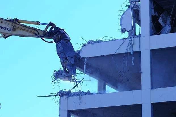 A backhoe tears into the Kinkead Building on Monday