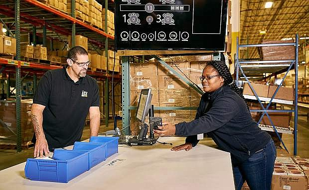 Chris Claudio, left, and Samantha Forbes check inventory scans at the ITS Logistics warehouse in Sparks.