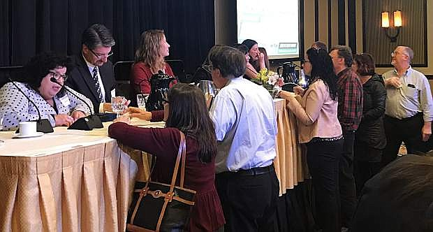 Panelists speak with attendees after the March 1 NNBW event.