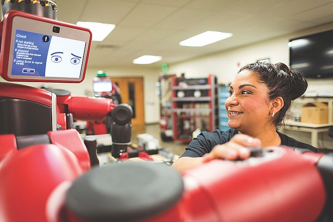 Truckee Meadows Community College student Cristina Tovalin learns to use a Baxter Collaborative Robot in the TMCC Advanced Manufacturing Lab last year.